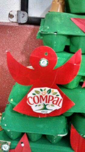 Detalhes de alguns enfeites de Natal onde se vê símbolos da marca Compal, Tetra Pak e FSC e materiais reutilizados com embalagens Tetra Pak, caixas de ovos e cápsulas de café.