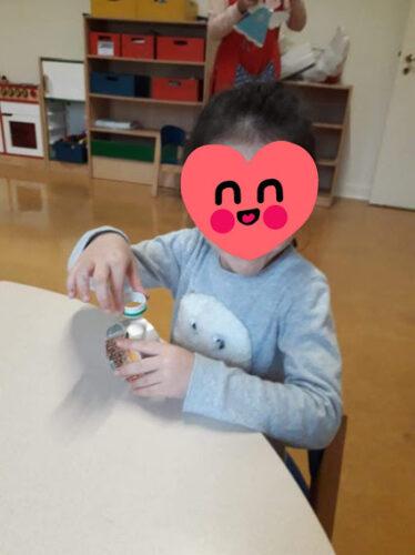"""Fotografia 2 - Elaboração do Boneco de neve <br/>Nesta fotografia podemos ver uma das crianças a colar o """"chapéu"""" do boneco de neve (utilizando a parte superior da embalagem onde se encaixa a tampa) na cabeça do boneco de neve (círculo criado com uma tira da"""