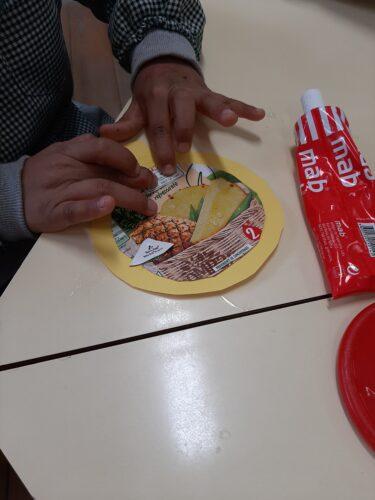 Colagem de bocadinhos da embalagem num papel autocolante para fazer uma bola predominantemente amarela.
