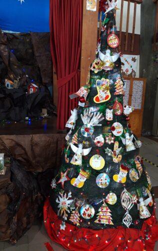 Árvore de Natal Ecológica<br/>A árvore de Natal ficou muito colorida e bastante bonita com os trabalhos reutilizados feitos pelas crianças.