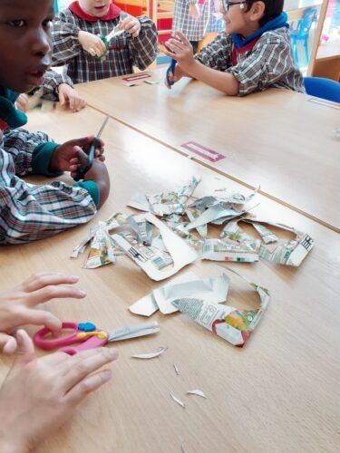 Sala das Estrelas - Crianças a recortarem os sinos de Natal dos pacotes de sumo COMPAL.