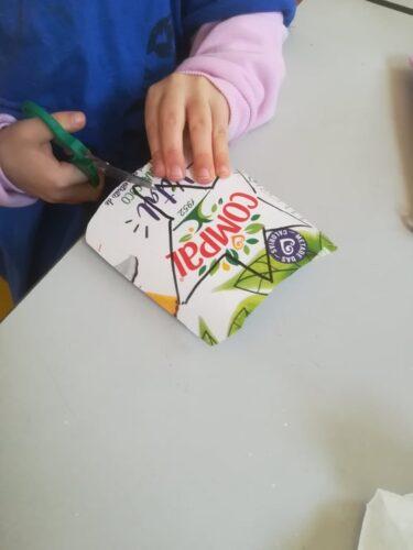 Criança a recortar um dos enfeites