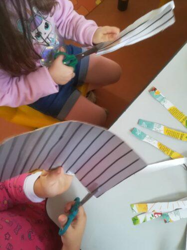 Crianças a recortar as tiras de embalagens Compal para depois construírem os enfeites