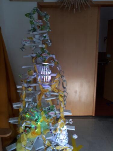 Vista do produto final, árvore decorada com os vários enfeites: argolas, juntas formando a corrente e utilização do tecido amarelo.