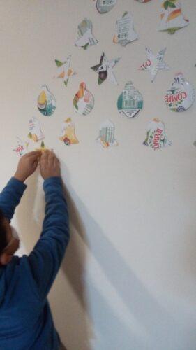 Aluno a colocar as decorações para formar um pinheiro na parede do refeitório.