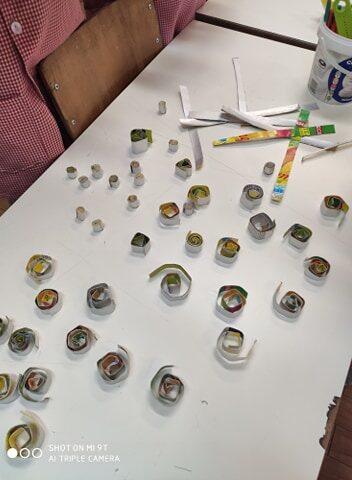 Corte das embalagens, em tiras, para a composição / construção dos enfeites natalícios, com recurso à técnica de quiling.
