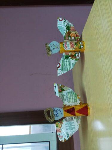 Anjos com rolos de papel, papel metalizado, cartão, fita dourada, e pacotes de Sumo Compal