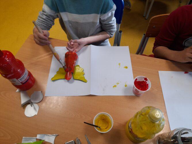 Pintura de alguns enfeites com as cores amarela e vermelho