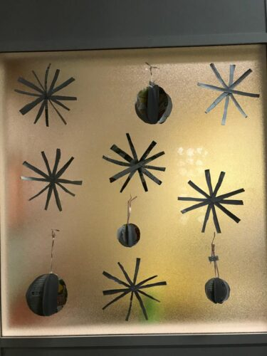 JANELA NATALICIA<br/>Decoração de uma janela com motivos natalícios realizados com círculos dobrados e tiras recortadas.