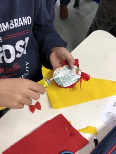 Pormenor de aluno a confecionar o seu enfeite com recurso a diversos materiais