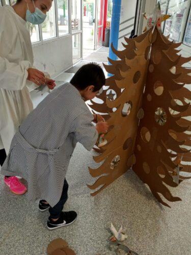 Colocação dos enfeites na árvore, construída com cartões.