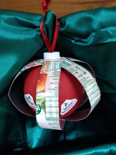 Usamos uma bola da máquina, forramos com papel vermelho, uma tampa de iogurte branca para ajudar a prender o fio e as tiras do cartão da compal. Esta bola representa a força união.