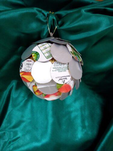 Usamos uma bola da máquina, pegamos no cartão da compal e desenhamos círculos pequenos, colocamos uns sobrepostos nos outros, forrando assim a bola inicial. Transmite a ideia de que juntos, de mãos dadas, conseguimos salvar a nossa natureza