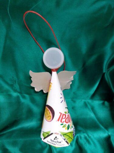 Usamos um pacote da compal, as asas foram feitas no mesmo material e para a cabeça tivemos a ideia de colocar uma tampa de iogurte branca. Este anjo simboliza a ingenuidade e alegria das crianças.