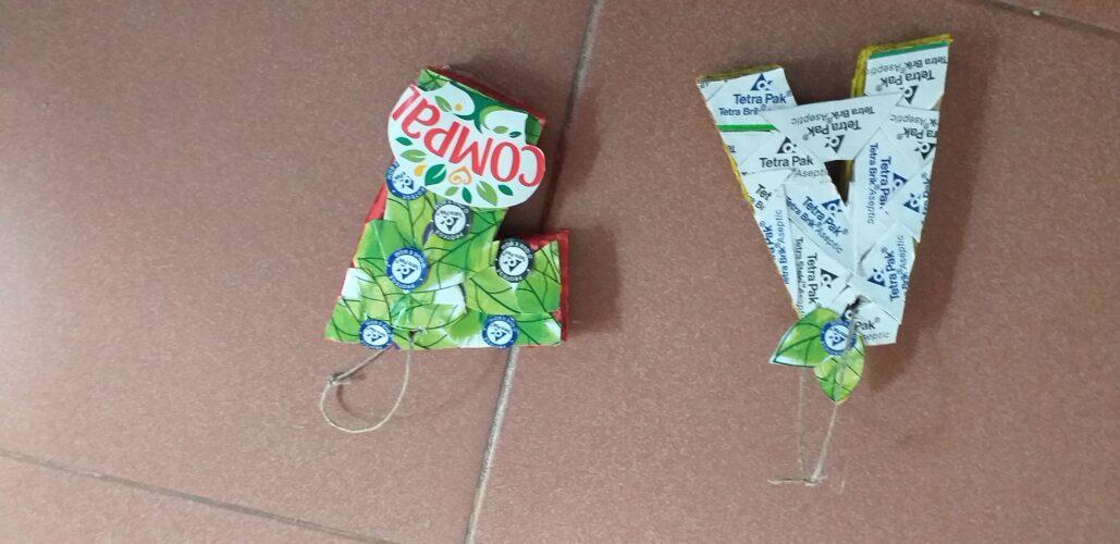 número e letra: cartão grosso, embalagens da compal e de leite, cola quente, tesoura, guache amarelo e vermelho para colorir a parte de trás.